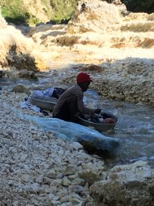 Photo of Haitian woman washing clothes in river